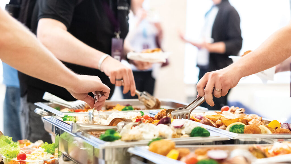 Closeup of people scooping food from trays at a buffet