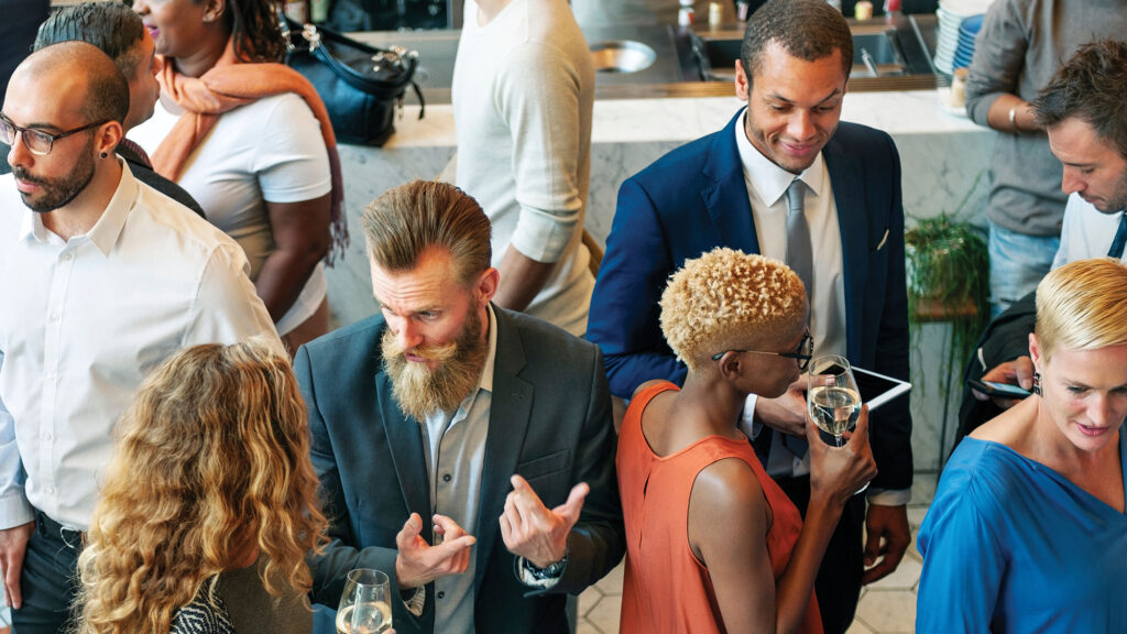 a diverse group of business people milling about at an event